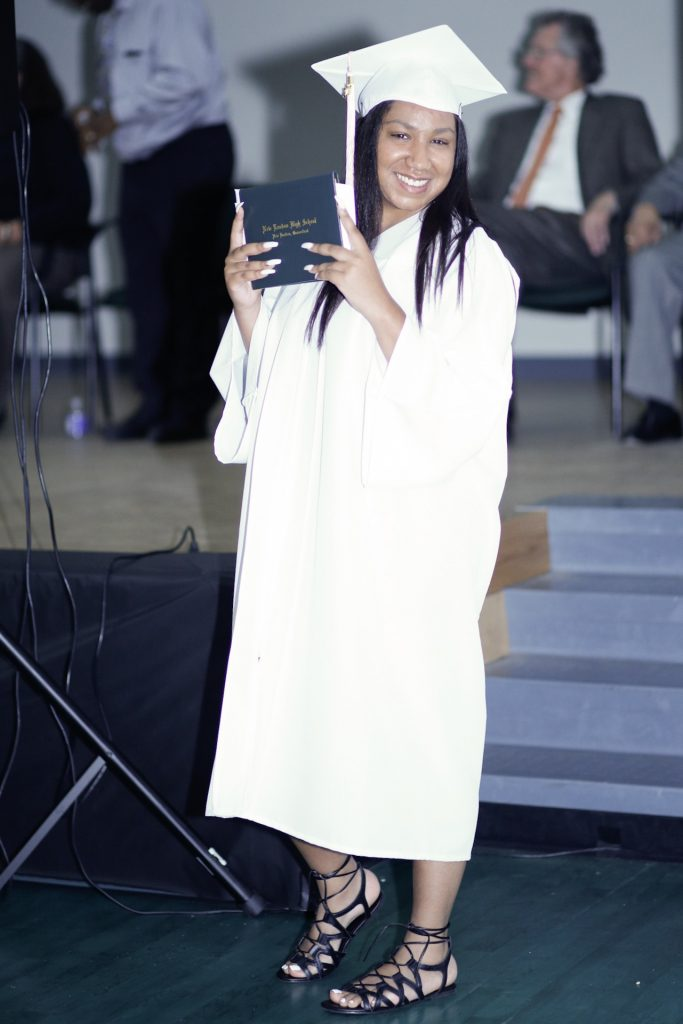 senior poses with high school diploma at commencement ceremony