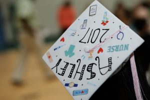 cap and gown decorated for high school graduation ceremony